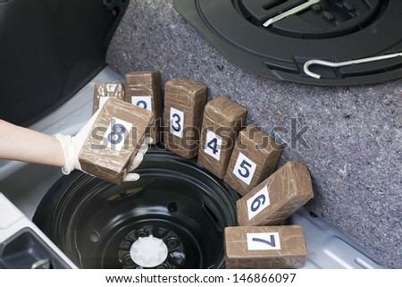 Drug smuggled in a car trunk  - stock photo