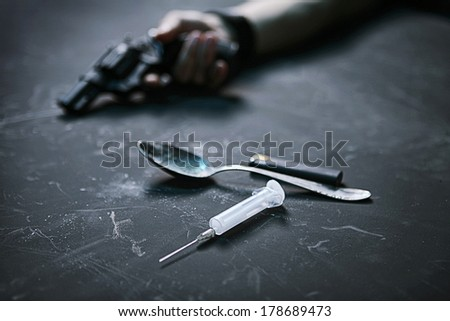Drug taker / studio photography of human hand with a gun, syringe, spoon and lighter on black background  - stock photo