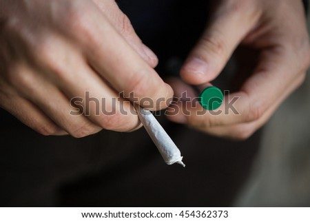 drug use, substance abuse, addiction, people and smoking concept - close up of addict hands with marijuana joint and blunt tube - stock photo