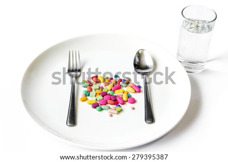 Drugs, medicine on a dish with fork , spoon and a water glass on white background. - stock photo