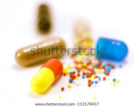 Drugs out of the capsule lying on a white background - stock photo