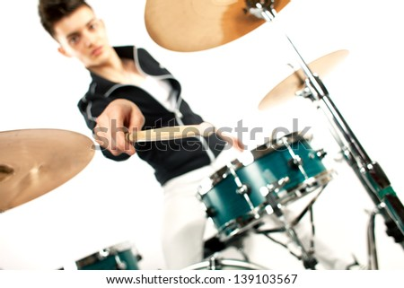 Drummer holding his drum stick in focus near drum set - stock photo