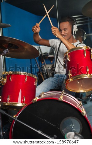 Drummer playing the drums in the studio - stock photo