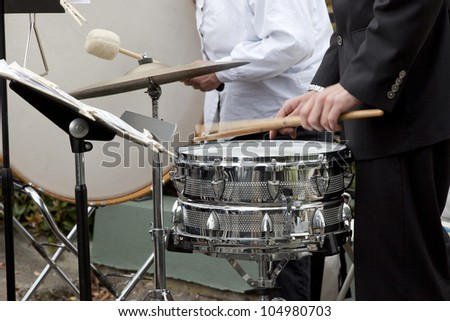 Drummer playing the snare drum, bass drum in background. - stock photo