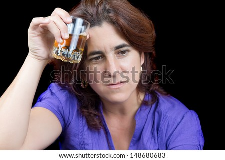 Drunk and sad latin woman holding a glass of liquor isolated on black - stock photo