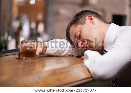 Drunk and unconscious businessman lying on counter. man sleeping after hard day in bar - stock photo