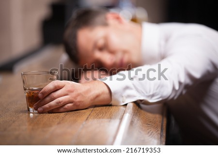 Drunk and unconscious guy lying on counter. man sleeping after hard day in bar - stock photo