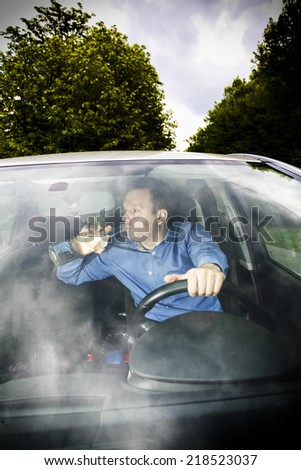 Drunk driver is drinking strong liquor from glass bottle during driving - stock photo