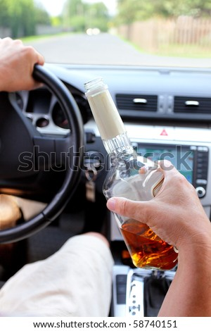 Drunk driver on a rural road with a bottle of alcohol in hand - stock photo