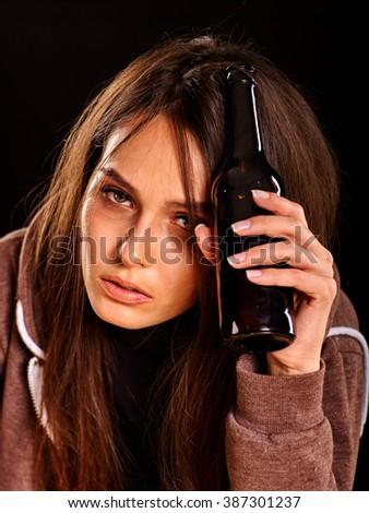 Drunk girl keeps bottle of alcohol. Soccial issue addict alcoholism. Black background. - stock photo