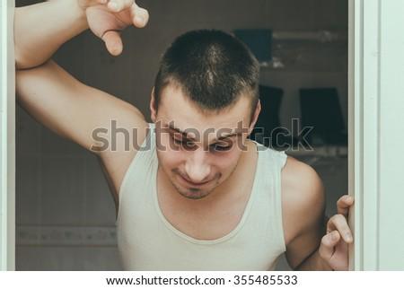 drunk guy barely standing near the door - stock photo