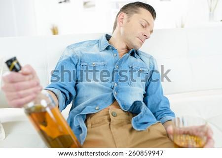 Drunk man on a sofa - stock photo