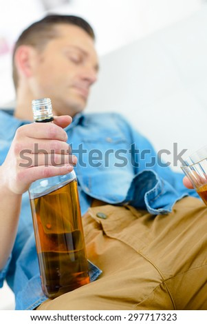 Drunk man on his sofa - stock photo