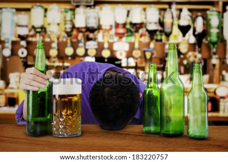 Drunk man sleeping in the bar, with bottle of beer in his hand - stock photo