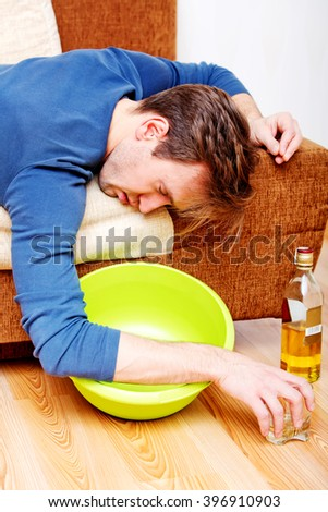 Drunk man sleeping on couch with whikey bottle and bowl - stock photo