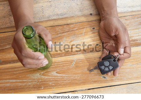 Drunk man sleeping on the table with beer bottle and car keys on his hand - stock photo