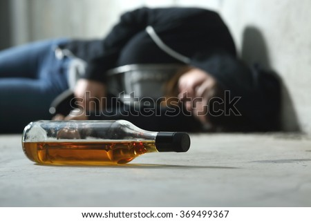 Drunk teenager on the floor in a dark and sad place and an alcohol bottle in the foreground - stock photo