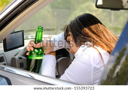 Drunk woman driver passed out in the car with her head resting on her arm on the steering wheel and her bottle of booze clasped in her hand - stock photo