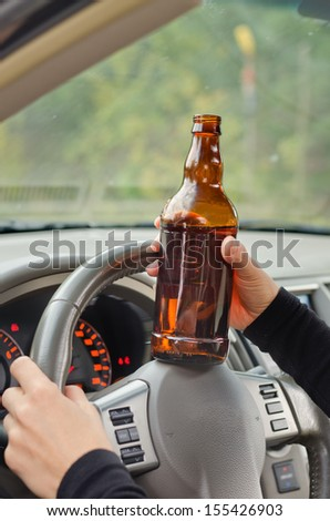 Drunk woman driver with a bottle of booze resting it on the steering wheel as she drives along creating a road hazard for motorists through her diminished capabilities - stock photo