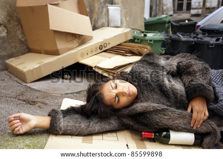 drunk woman lying in trash with bottle of wine - stock photo