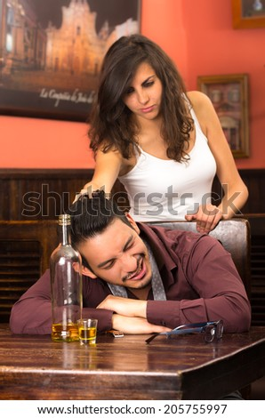 drunk young man sleeping and angry girlfriend in a bar pulling his hair - stock photo