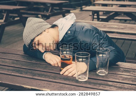Drunk young man sleeping at pub in London. He is sitting at table outdoor with some empty glasses on the table. - stock photo