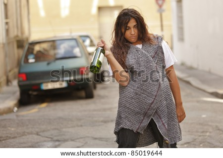 drunk young woman holding bottle of wine walking in city street - stock photo