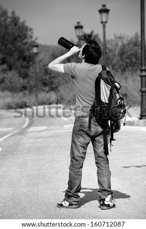 Drunkard walking around the streets boozing from a bottle - stock photo