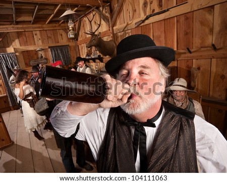 Drunken man chugs a bottle of alcohol in a saloon - stock photo