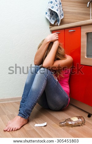 Drunken woman at the kitchen - stock photo