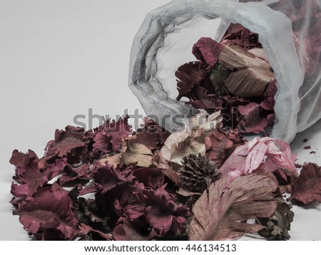 dry aromatic flowers and spices spilling out of a bag, vintage tone - stock photo