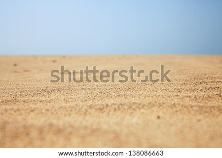 Dry beach sand and clear blue sky close-up - stock photo