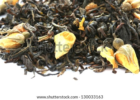 Dry black tea flavored with dry flower buds on white background - stock photo