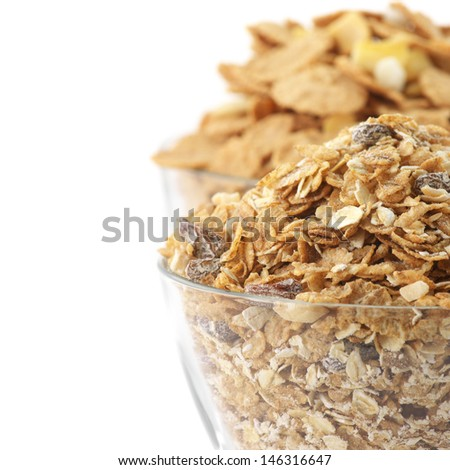 Dry breakfast cereal in glass bowls on white background. - stock photo