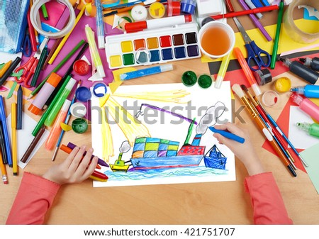 dry cargo ship with containers, transportation concept, child drawing, top view hands with pencil painting picture on paper, artwork workplace - stock photo