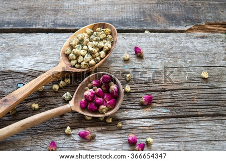 Dry chamomile and rose tea on a wooden spoons - stock photo