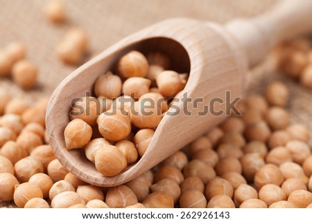 Dry chickpeas healthy nutrition food in wooden spoon on vintage texile background - stock photo