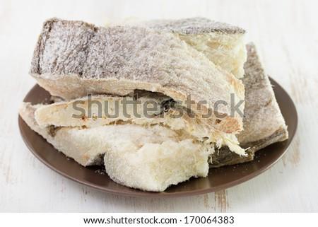 dry codfish on dark plate - stock photo