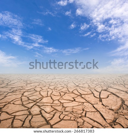 Dry cracked soil in drought land under blue sky. - stock photo