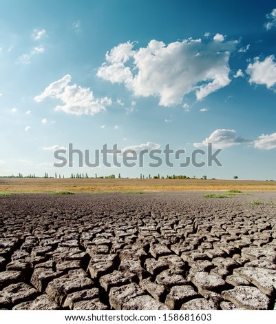 dry desert under blue sky with clouds - stock photo