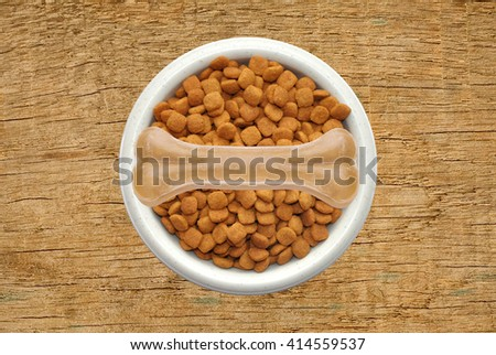 Dry dog food and bone in plate over wooden texture  - stock photo