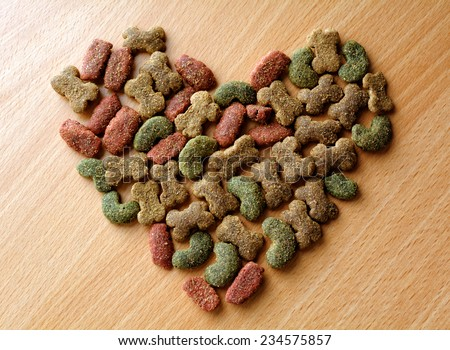 Dry dog food in heart shape on the table - stock photo