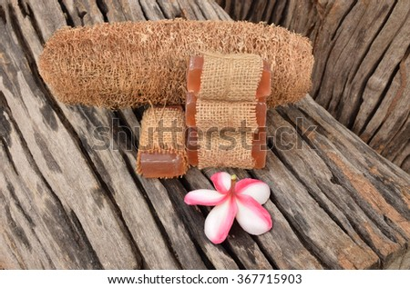 Dry fiber of zucchini and honey soap spa wrapped with hem sack cloth  on the old wood texture.Selective focus with shallow depth of field. - stock photo