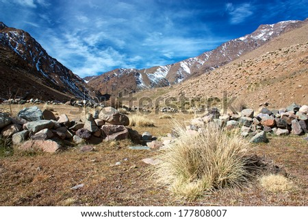 Dry grass turf and rocks in High Atlas mountains with bits of snow - stock photo