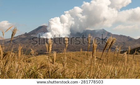 Dry grass with View Smoke Gas Steam Crater of Mount Aso Volcano Caldera largest active Volcano in Japan Island eruption under Sunny Clear Blue Sky in Summer Daytime, Kumamoto, Kyushu - stock photo