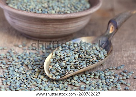 Dry green french lentils (Du Puy) in a clay bowl and in a scoop on wooden table, selective focus - some beans in focus, some are not - stock photo