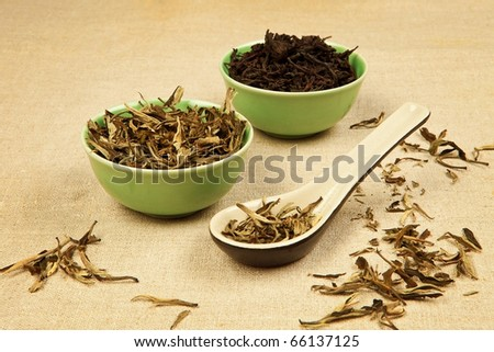 Dry green tea and black tea leaves arranged on brown background. - stock photo