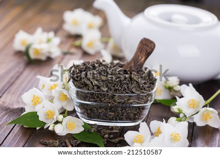 Dry green tea with jasmine on wooden background. Selective focus. - stock photo