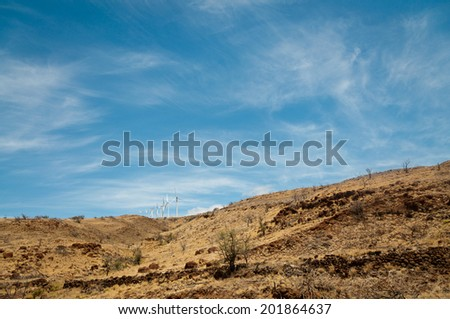 Dry hill on Maui with a row of wind turbines - stock photo