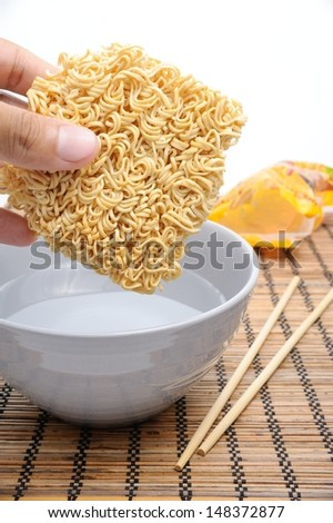 dry instant noodles over boiled water in bowl - stock photo